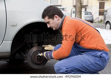 mechanic checking worn car brake - stock photo
