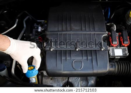 mechanic checks coolant liquid level  - stock photo