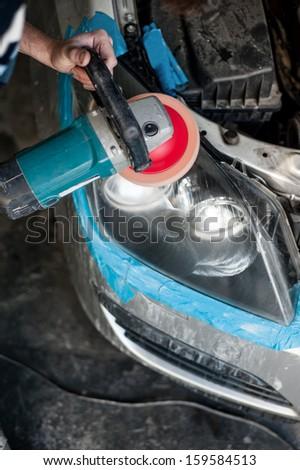 mechanic cleaning headlights with polishing power buffer machine - stock photo