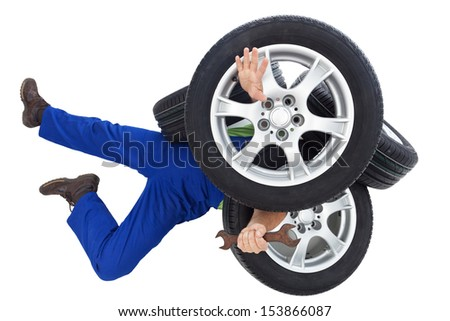 Mechanic covered by car tires - on white background - stock photo