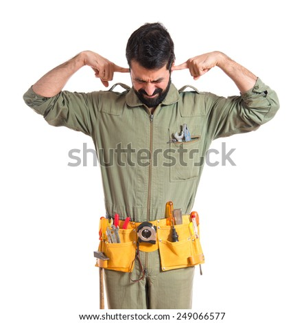 Mechanic covering his ears  - stock photo