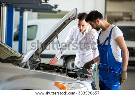 mechanic discussing with customer in garage - stock photo