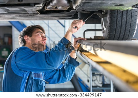 Mechanic, examining the suspension of a vehicle with a steel rod for any undesired clearances as part of a periodical vehicle safety inspection or mot test - stock photo