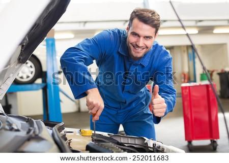 Mechanic examining under hood of car at the repair garage - stock photo