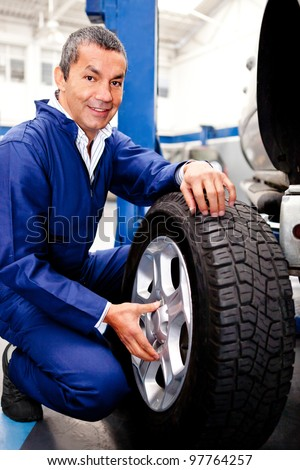 Mechanic fixing a car puncture holding a wheel - stock photo