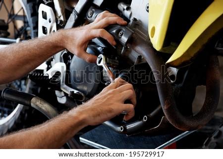 mechanic fixing motocycle engine - stock photo