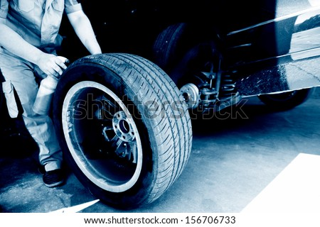 mechanic hands with tool repairing the car at garage. - stock photo