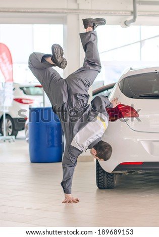Mechanic having fun in car dealership. - stock photo