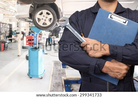 Mechanic holding a clipboard of service order and wrench for maintaining car on lift at the repair shop - stock photo