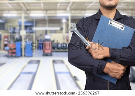 mechanic holding a clipboard of service order with wrench at the repair shop - stock photo