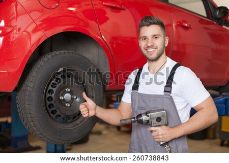 Mechanic holding an impact wrench and showing thumb up - stock photo