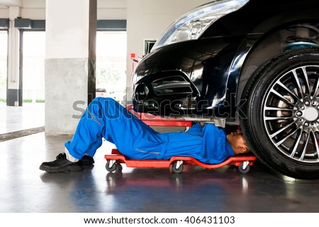 Mechanic in blue uniform lying down and working under car at auto service garage - stock photo
