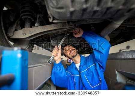 mechanic in overalls working under  car - stock photo