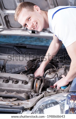 mechanic in uniform checks a car engine - stock photo