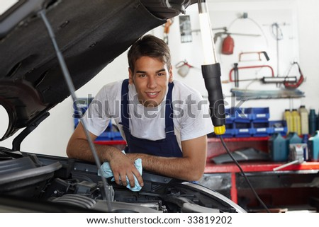 mechanic leaning on bonnet and looking at camera - stock photo