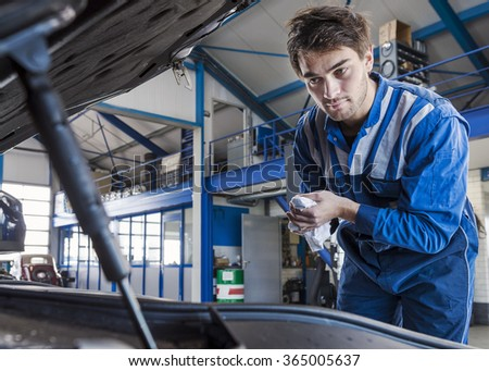 Mechanic looks under the hood of a car, washing his hands with a towel from the oil. - stock photo