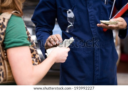 Mechanic: Man Takes Cash As Payment From Customer - stock photo