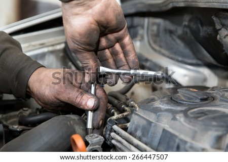 mechanic man worker with socket wrench during car repair works in auto service center - stock photo
