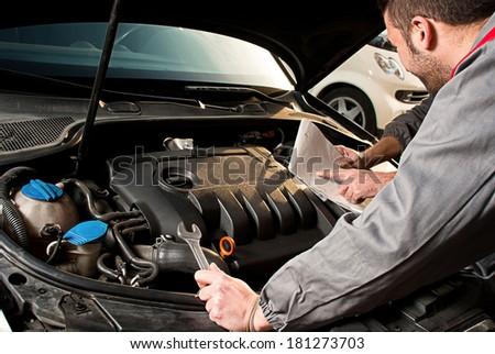Mechanic. Mechanic decides how to repairing an engine. - stock photo