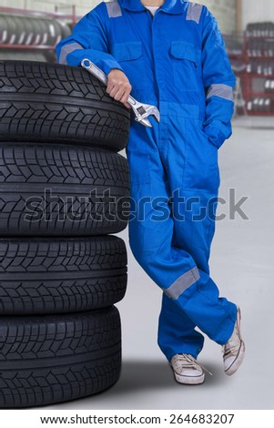 Mechanic person with blue uniform, standing in the workshop while holding a wrench and leans on tires - stock photo