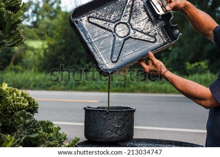 Mechanic Pouring gasoline into the tank - stock photo