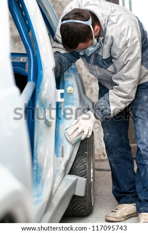 mechanic preparing the car for painting - stock photo