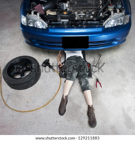 Mechanic repairing a car in a garage - stock photo