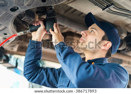 Mechanic repairing a lifted car - stock photo