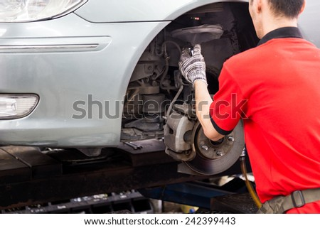Mechanic repairing the wheel area of a vehicle in a workshop - stock photo