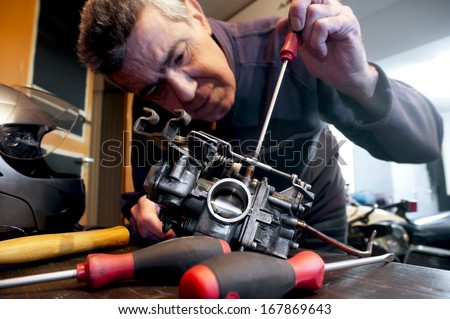 Mechanic repairs the carburetor of his motorcycle - stock photo