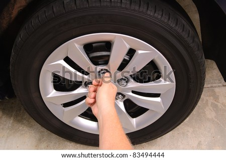 Mechanic replacing lug nuts by hand while changing tires on a vehicle. - stock photo