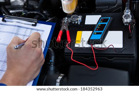 Mechanic's hand writing on clipboard with pliers connected to multimeter on car engine - stock photo