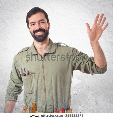 Mechanic saluting over textured background  - stock photo