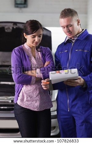Mechanic showing the quotation to a woman in a garage - stock photo
