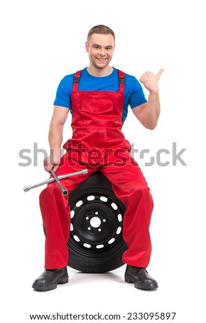 mechanic sitting on tire and showing thumb up. happy man smiling into camera on white background - stock photo