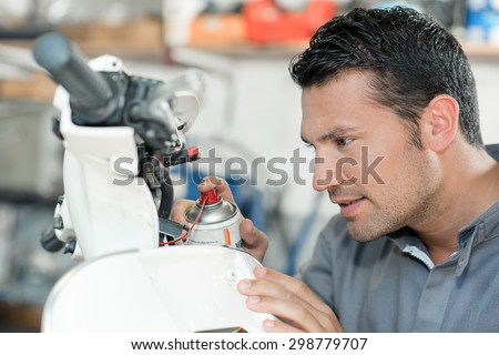 Mechanic spraying lubricant on a scooter - stock photo