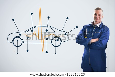 Mechanic standing in front of a background with car diagram on it - stock photo