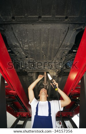 mechanic standing under car engine and holding lamp. Copy space - stock photo