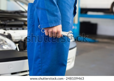 Mechanic standing with wrench in hand at the repair garage - stock photo