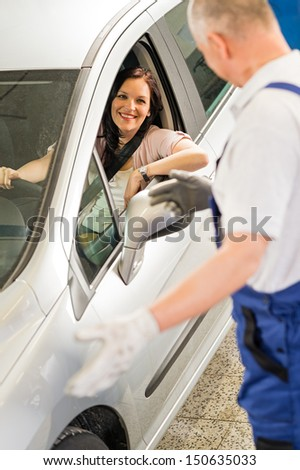 Mechanic talking with satisfied car owner - stock photo