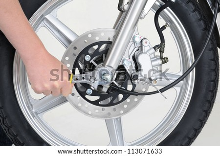 mechanic tightening the wheel nut on a motorcycle - stock photo