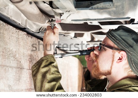 Mechanic Under Car Installing Exhaust Pipe - stock photo