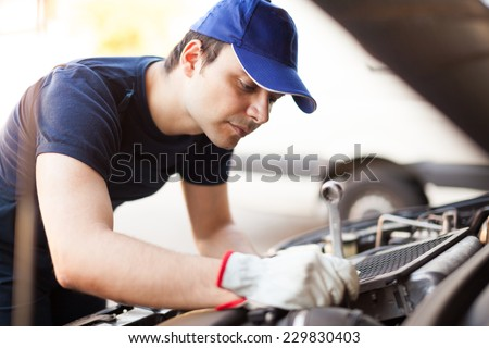 Mechanic using a wrench to repair a car engine - stock photo