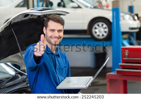 Mechanic using his laptop showing thumbs up at the repair garage - stock photo
