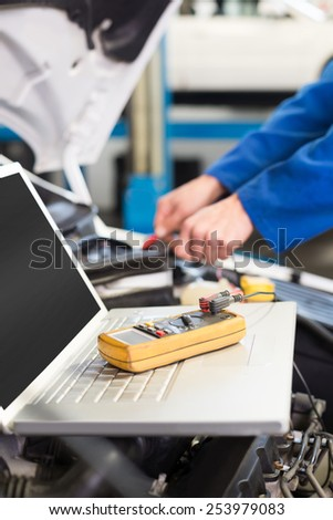Mechanic using laptop on car at the repair garage - stock photo