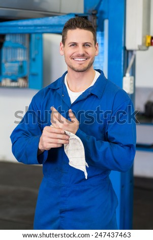 Mechanic wiping hands with rag at the repair garage - stock photo