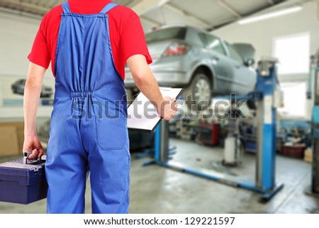 Mechanic with a tool box and clipboard standing in a car repair service - stock photo