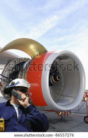 mechanic with large jet engine in background, airport maintenance works - stock photo