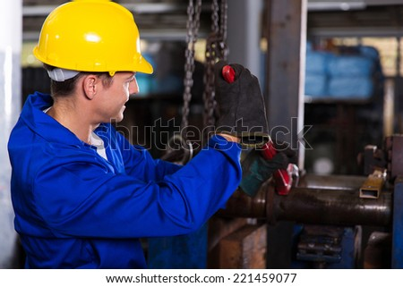 mechanic with monkey wrench repairing factory pipes - stock photo