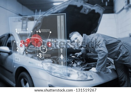 Mechanic with open hood consulting futuristic interface with diagram - stock photo
